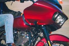 Rowerzysta jedzie czerwonego motocykl w cajgach Boczny widok obrazy royalty free