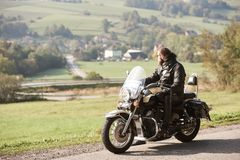 Rowerzysta jedzie nowożytnego potężnego motocykl wzdłuż pogodnej drogi na letnim dniu w czarnym rzemiennym stroju fotografia stock