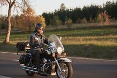 Rowerzysta jedzie nowożytnego potężnego motocykl wzdłuż pogodnej drogi na letnim dniu w czarnym rzemiennym stroju obraz stock