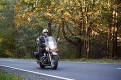 Rowerzysta jedzie nowożytnego potężnego motocykl wzdłuż pogodnej drogi na letnim dniu w czarnym rzemiennym stroju zdjęcie royalty free