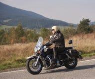 Rowerzysta jedzie nowo?ytnego pot??nego motocykl wzd?u? pogodnej drogi na letnim dniu w czarnym rzemiennym stroju fotografia stock