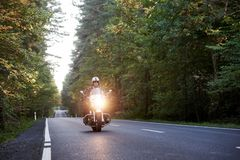 Rowerzysta jedzie nowo?ytnego pot??nego motocykl wzd?u? pogodnej drogi na letnim dniu w czarnym rzemiennym stroju zdjęcia stock