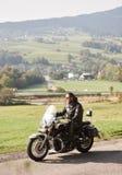 Rowerzysta jedzie nowo?ytnego pot??nego motocykl wzd?u? pogodnej drogi na letnim dniu w czarnym rzemiennym stroju zdjęcie royalty free