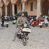 Rowerzysta jedzie rocznik hulajnoga włoskiego Vespa Zdjęcie Royalty Free