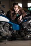 Rowerzysta kobieta stoi blisko jej motocyklu z ciężką budową, opierający siedzenia, patrzeje kamerę zdjęcia royalty free