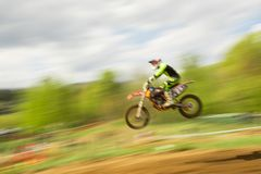 Rowerzysta na motocross skoku w ruchu Zdjęcie Stock