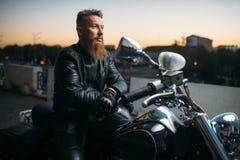 Rowerzysta pozy na motocyklu w mie?cie na zmierzchu obraz stock