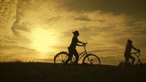 Rowerzysta rodzinna sylwetka, rodzice z dwa dzieciakami na rowerach przy zmierzchem Poj?cie ?yczliwa rodzina zdjęcie wideo