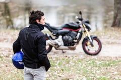 Rowerzysta stoi blisko motocyklu trzyma jego błękitnego hełm zdjęcia stock