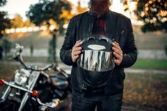 Rowerzysta trzyma hełm w rękach, siekacz na tle obrazy stock