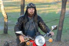 Rowerzysta w skórzanej kurtce i hełm na retro motocyklu w lesie obrazy stock