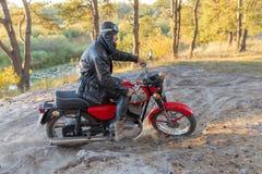 Rowerzysta w skórzanej kurtce i hełm na retro motocyklu w lesie obraz royalty free
