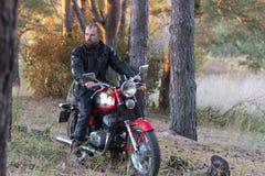 Rowerzysta w skórzanej kurtce i hełm na retro motocyklu w lesie fotografia royalty free