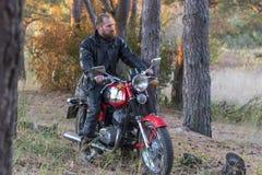 Rowerzysta w skórzanej kurtce i hełm na retro motocyklu w lesie zdjęcia royalty free