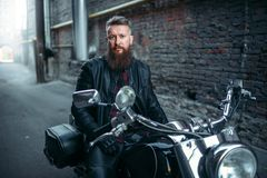 Rowerzysta w skórzanej kurtce na klasycznym siekaczu obraz royalty free