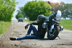 Rowerzysta w stroju siedzi obok jego motocyklu na drodze fotografia stock