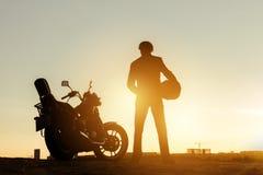 Rowerzysta z motocyklem przy zmierzchu czasem obraz stock