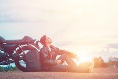 Rowerzysty mężczyzna pozycja dymi z jego motocyklem obok naturalnego jeziora i piękny, cieszący się wolność i aktywnego styl życi Zdjęcie Royalty Free