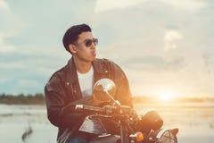 Rowerzysty mężczyzna pozycja dymi z jego motocyklem obok naturalnego jeziora i piękny, cieszący się wolność i aktywnego styl życi Zdjęcia Royalty Free