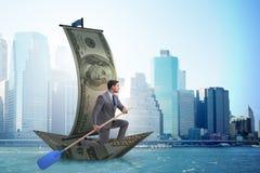 Rowing бизнесмена на шлюпке доллара в концепции дела финансовой Стоковое Изображение RF