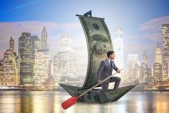 Rowing бизнесмена на шлюпке доллара в концепции дела финансовой Стоковые Изображения