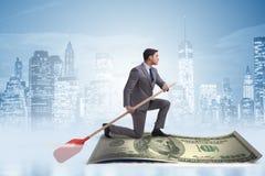 Rowing бизнесмена на шлюпке доллара в концепции дела финансовой Стоковые Изображения RF