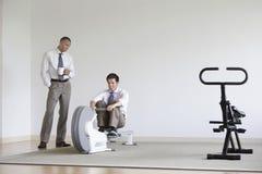Машина rowing пользы коллеги бизнесмена наблюдая Стоковые Фотографии RF