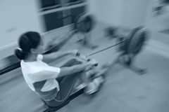 Rowing. Girl exercising in the gym royalty free stock photo