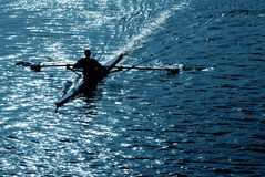 Rowing alone. Silhouette of man rowing alone Stock Photos