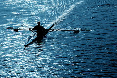 Rowing alone in blue Stock Photography