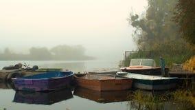 Rowing-barco viejo de la pesca en el embarcadero en el agua metrajes