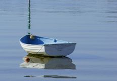 Rowing Boat. Blue and white rowing boat or tender with reflections moored in lake Stock Photography