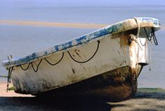 Rowing boat. A rowing boat on shore, pulled up beyond the reach of high tide stock photo