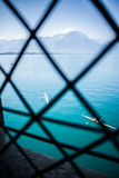 Rowing boat and Alps. View through window onto the French Alps covered in Snow with lake geneva and boats in the foreground Royalty Free Stock Photography