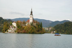 Rowing boat approaching the island on Bled lake Stock Photo
