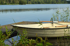 Rowing boat on a calm lake. A little white rowing boat rests by the side of a calm lake, anchored by a small wood pier among green pond reeds. In the background royalty free stock image