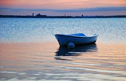Rowing boat in calm reflecting sea. A small boat in a calm evening. From Oland Sweden with Kalmar skyline in background Stock Photo
