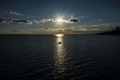 Rowing boat caught in the beam of light of a lowering sun. Southend on Sea, Essex royalty free stock image