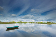 Rowing boat floating on a small lake in The Ooijpolder by Nijmegen, Holland. Rowing boat floating on a small lake in The Ooijpolder during spring on a sunny day Stock Photos