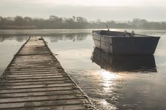 A rowing boat floats adrift on a frozen lake beside an empty walkway royalty free stock image