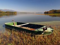Rowing boat by lake. Wooden rowing boat moored by side of picturesque lake in countryside stock image