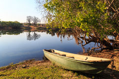 Rowing boat lying on the banks of a river lit by sun Stock Photo
