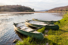 Rowing boat lying on the banks of a river lit by sun Stock Photography