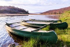 Rowing boat lying on the banks of a river lit by sun Stock Image