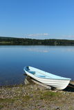 Rowing boat moored on calm lake shore Stock Photo