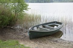 Rowing boat moored lake loch reeds single one lonely scenic national park uk Royalty Free Stock Image