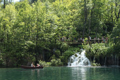 Rowing boat in one of Plitvice's lakes and people walking on a path Stock Images