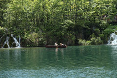 Rowing boat in one of Plitvice's lakes and people walking on a path Royalty Free Stock Photography