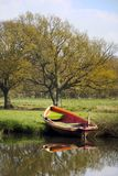Rowing boat on river bank. A painted wooden rowing boat is moored on the banks of the river Wey in the UK. The boat is reflected in the calm water and a field royalty free stock images