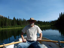Rowing a boat in the rocky mountains Royalty Free Stock Photo